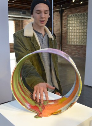 Senior Josh Goering pretends to touch one of the pieces in the gallery. Photo by Annie Lomshek.