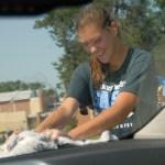 Junior Jillian Gaunt dries a car windshield. Photo by Tess Iler