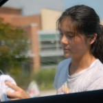 Freshman Lia Miller dries a car mirror. Photo by Tess Iler