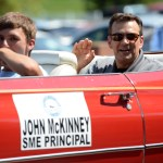 Principal John McKinney waves at students lining the sidewalks of Mission Road. Photo by Joseph Cline