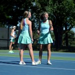 Doubles partners Joie Freirich and Lucy Kendall talk on the court after winning their match. Photo by Maddie Smiley