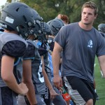 Assistant Freshmen Coach Kyle Ball gives the freshmen boys strategy on how to perform a successful tackle. Photo by Abby Blake