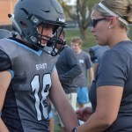 Freshman Gibson Breyer gets advice from Athletic Director Megan Burki after hurting his arm during a tackle. Photo by Abby Blake