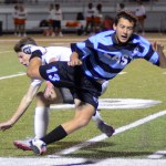 Senior Lucas Adel trips over his opponent while fighting for control of the ball. Photo by Kaitlyn Stratman