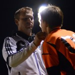 Coach Williams looks at Senior Thomas Allegri's lip after he hurt it while defending the goal. Photo by Kaitlyn Stratman