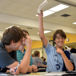 Sophomores Zach Krause, Owen Burrows and Julius Von Rautenfeld laugh as they hold up their answer. Photo by Anna Kanaley