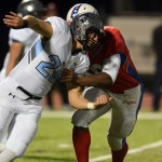 Junior Eli McDonald attempts to get past Olathe North's offensive lineman. Photo by Morgan Browning