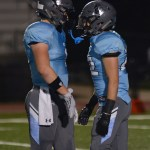 Sophomore Milton Braasch and Senior Rider Terry head-butt to get pumped for the next play. Photo by Annie Lomshek