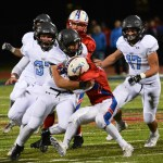 Junior Eli McDonald blocks an Olathe North player from rushing the ball as East teammates gather to help with the tackle. Photo by Haley Bell