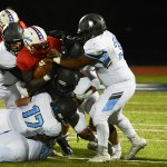 Defensive players work together to tackle Olathe North's running back. Photo by Haley Bell