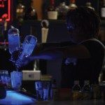 The bartender prepares a drink while conversing with a group at the bar. Photo by Kaitlyn Stratman