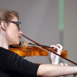 Senior Lilly Wulfmeyer plays the violin during the symphonic orchestra's performance.  Photo by Tess Iler