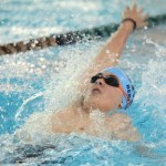 Freshman Aaron Berlau competes in the 100 yard backstroke. Photo by Haley Bell