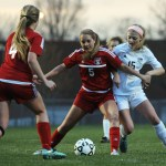 Sophomore Maddy Muther is blocked out by a Shawnee Mission North player as she attempts to take the ball. Photo by Haley Bell