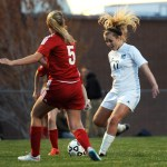 Senior Chloe Harrington passes the ball to a teammate to avoid a Shawnee Mission North defender. Photo by Haley Bell