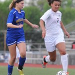 Senior Georgia Weigel blocks an Olathe South defender as she dribbles down the field. Photo by Haley Bell