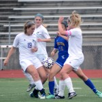 Seniors Claire Schreiber and Chloe Harrington fight an Olathe-South player for the ball while it is in the air. Photo by Kaitlyn Stratman