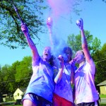 Sophomores Audrey Kessler, Kaleigh Koc, and Kirsten Erickson throw up color as they take a go-pro video. Photo by Ellie Thoma