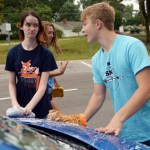 Sophmore Ali Nedblake and Sophmore Luke Hoffman wash the hood of a car. Nedblake reacts to Hoffman trying to splash her. Photo by Elizabeth Anderson.