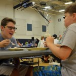 Two middle schoolers share a laugh over pancakes. Photo by Lizzie Kahle