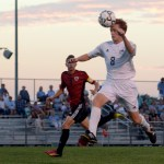 Junior Tommy Nelson jumps into the air to header the ball. Photo by Diana Percy