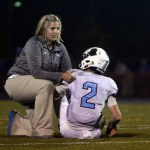 During the tackle, Kaiser is hurt, so trainer Megan Burki makes sure he is okay before helping walk off the field. Photo by Kaitlyn Stratman