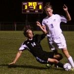 Senior Clayton Phillips tries to make it past an Olathe Northwest defender. Photo by Sophie Storbeck