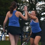Senior Emily Walter and sophomore Emily Cooper high-five ater winning a game in their second set. Photo by Morgan Plunkett