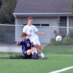 Sophomore Carson Jones collides with a player from Olathe East after he passes the ball. Photo by Katherine Odell