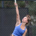 Freshman Caroline Chisholm makes contact with the ball while serving. Photo by Ellen Swanson