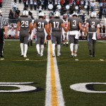 The football captains hold hands and walk to the center of the 50 yard line to do the coin toss. Photo by Annie Lomshek