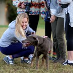 Junior Alyssa Vuillemin bends down to pet the silver lab that Milton Braasch brought to the practice. Photo by Kaitlyn Stratman