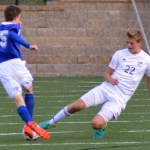 Sophomore Parker Willis defends the goal and kicks the ball away from his apponent. Photo by Izzy Zanone