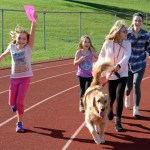 Senior Sarah Milgrim and her sisters run with their dog around the track to win the Dog Dash. Photo by Ellie Thoma
