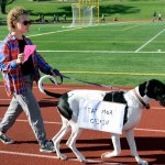 Junior Riley McCulliugh walks her dog, who is dressed as a the Chik-fil-A mascot, around the track during the Dog Dash. Photo by Ellie Thoma