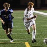 Junior Tommy Nelson dribbles the ball down the field as he attempts to avoid his defender. Photo by Haley Bell