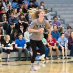 Junior Maddy Muther runs to stack her can in the can stacking race competition against the other grades. Photo by Katherine Odell