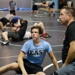 Junior Andrew Schmit and Coach Goodson watch as pairs pratice drills at boys wrestling tryouts. Photo by Katherine Odell