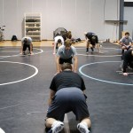 The boys at wrestling tryouts watch as their coach Mr. Goodson shows them watch they will do next. Photo by Katherine Odell
