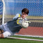 Junior keeper, Nick Gasperi, saves the ball while warming up during half time. Photo by Kaitlyn Stratman