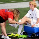 Junior Ian Schutt winces in pain as the athletic trainer wraps his ankle. Photo by Kaitlyn Stratman