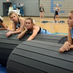 Sophomore Laura Ratley-Bazea , Junior Chloe Kowalski, and Junior Ava Meng rest on the mats as the attempt to roll them up. Photo by Ellie Thoma