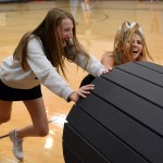 Sophomores Payton Johnson and Maggie Gray laugh as they struggle to push the mat out of the gym. Photo by Ellie Thoma
