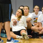 The girls trying out for basketball listen intently to Coach TJ. Photo by Ellie Tjhoma