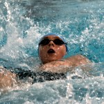 Freshmen Parker McElhinney swims the 100 Backstroke. Photo by Laini Reynolds