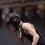 Freshman Charlie Voyset fixes his headgear at the beginning of the first period of his match. Photo by Celia Hack