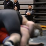 Assistant wrestling coach Dustin Delaney watches sophomore Cooper Lovelace as he wrestles. Photo by Celia Hack
