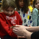 Senior Blake Johnson hands a girl a tarantula as her classmates watch. Photo by Ty Browning