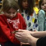 Senior Blake Johnson hands a girl a tarantula as her classmates watch. Photo by Ty Browning