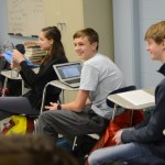 After one of his classmates makes a joke in their presentation, sophomore Tom Joyce laughs with his friends. Photo by Grace Goldman